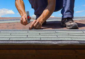 gardener renew roof of summer garden house with tar paper shingles